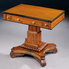 An Antique William IV Games Table  Of oblong form in softly faded mahogany with an ebonised thumb moulded edge, the diagonally opposed drawers for counters and chessmen flanking the central drawer, which has been fitted with inset chess and backgammon boards. Standing on a two part stepped central column, of square and tapering sections, with an incurved quadripartite base, edged with gadrooning, with scrolled feet, and stylised acanthus bronze strapping to the sides