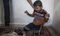 A young Palestinian boy reacts as he sees the body of a relative who died when a UN school used as a shelter for internally displace people came under Israeli shelling in Jabalia, northern Gaza Strip on 30 July 2014.