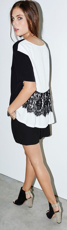 This black and white top begins with a simple solid front beforing turing into a white back with a panel of lace and a ruffle hem for a flirty exit.