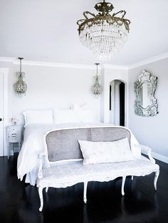 Crystal chandeliers x 3, decorative frameless glass mirror, an antique settee, and white.  fresh and glamorous.