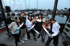 Description of . The crew of the pirate boat Mystic Maiden strike a pose before the Parade of Lights. Alex Schmitt , Tom Schmitt, Cathy Schmitt,  Annette Charbonneau, Christina Charbonneau,  Jean Parke and Mario Charbonneau . The Macomb Daily—David Dalton
