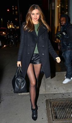 BYLINE: EROTEME.CO.UK.Miranda Kerr returns to her apartment from an all day photo shoot wearing black shorts and a black coat.