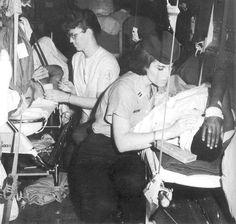 AF nurse tending to wounded service member on medevac flight, Vietnam.
