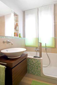Waschtisch Aus Holz Mit Runden Aufsatzwaschbecken, Dahinter Badewanne Mit  Tür, An Der Front Grüne