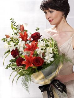 Featuring red asiatic lilies, red large headed roses and ivory mini cymbidium orchids expertly arranged with aralia, draceana sanderiana, trailing asparagus fern and eucalyptus and finished with gift wrap and ribbon by Flowers.ie. Order Flowers Ireland