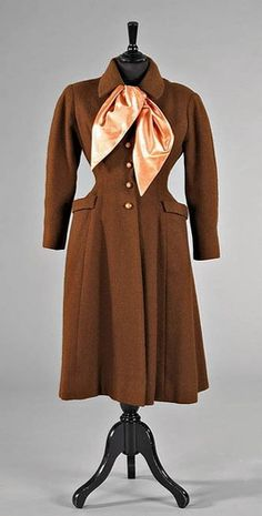 Christian Dior coat from autumn/winter 1952  In style it is very similar to the double-breated coat, although not double-breasted  Symmetrical, Long, Casual Feel, Cozy, Transitional Piece  Would fit nicely over a dress, popular for women of that time period