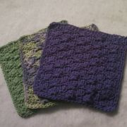 Shell dishcloths in sage green, variegated, and purple.