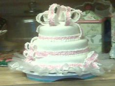 Three small tier of white dressed in Lacey pink and white ribbons and bows, is it a Birthday cake or shower cake you choose