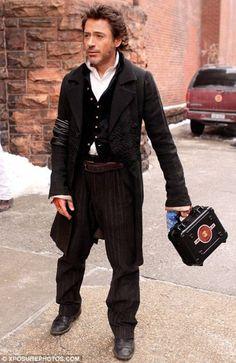 Robert Downey Jr. dressed as Sherlock carrying an Iron Man lunch box.