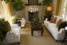 Living room featuring white couch and matching chairs with ornate dark wood coffee table and stone hearth.