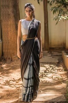 Half and half magic in an ever stylish shibori! A soft drape in black satin cotton with grey black shibori dyed pure satin cotton half. Fabulously detailed with a silver pom pom edging. An incredibly stylish saree this...Create a stir with a silver blouse or tone it down with a grey or a black blouse. Either way you'll look like a Diva in this drape! #houseofblouse #saree #blouse #indianwear #india #fashion #bollywood #black #grey #shibori #halfandhalfsaree