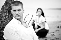 iPHOTOS.com - A beautiful caucasian couple in love sitting on the beach (in black and white)