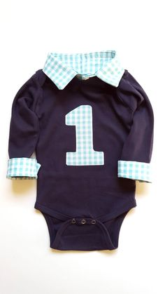This super cute collared bodysuit will have your baby boy looking dapper for his first birthday or photo shoot! This bodysuit features a faux collar and wrist cuffs for an effortless, preppy look! Add an applique to show off his birthday year! Bodysuit is navy and the gingham print is aqua.  **Size Chart** Preemie= Up to 5 lbs Newborn= 5 - 8 lbs 0-3M or 3M= 8 – 12.5 lbs 3-6M or 6M= 12.5 – 16.5 lbs 6-9M or 9M= 16.5 - 20.5 lbs 9-12M or 12M= 20.5 - 24.5 lbs 6-12M= 17-24 lbs 12-18M or 18M= 24.5…