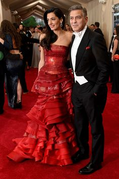 """Amal Alamuddin is wearing a strapless red John Galliano dress that was obviously inspired by the """"Chinese Whispers: Tales of the East in Art, Film, and Fashion"""" theme. George Clooney keeps it old school classic with a white tie evening tux with tails and a pop of coordinating red in his pocket."""