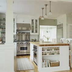 Airy white kitchen with glass front cabinets, butcher block island, open floor plan, upper shelving, spice storage, oven in island.