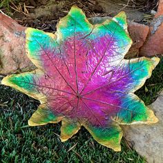 Hand cast leaf, decorative plate or outdoor garden ornament. 13H x 13W Metallic green and yellow and fuchsia. The beautiful custom blend of metallic colors bring this piece to life to enjoy year round. Has a small hole in the center for drainage do that water doesnt collect when sitting in your garden. Every Hauteleaf design is an Individually cast, one of a kind, hand painted piece. The magic begins by choosing the perfect leaf and casting it in an exclusive mixture of cement and bonding…
