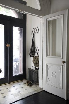 The entryway features the original marble floor and a new slim radiator from Governale. Double doors, think about tiles for the floor.