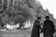 Hungarian civilians stand in the street as Budapest burns. Part of the broader Budapest Offensive, the siege of the city began when Budapest, defended by Axis Hungarian and German troops, was first encircled on 29 December 1944 by the Soviet Army and the newly Allied Romanian Army. The siege ended when the city unconditionally surrendered on 13 February 1945. Budapest, Hungary. February 1945. Image taken by Yevgeny Khaldei.