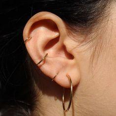 Combinação de brincos e piercings na orelha