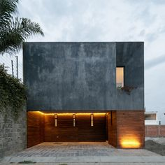 Espacio 18 has made the most of a narrow site in Puebla, by incorporating a bright internal courtyard and a rooftop patio into a dark-rendered residence.