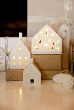 Winterzeit. Krippe.  Weißes Porzellan lässt das Licht der Kerze durchscheinen und die Silhouetten der Krippenszene sichtbar werden.