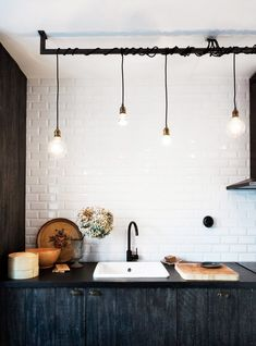 In this Scandinavian kitchen, wires are shamelessly entwined on a rod, a look sometimes referred to as a hanging light collage.