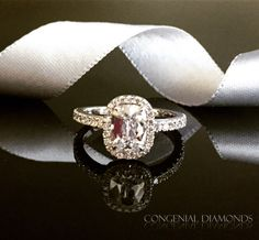 A superb vintage diamond engagement ring with a cushion cut diamond and very sparkling halo and diamond shoulders