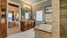 Treat yourself to an evening of bliss in your tranquil master bathroom with stunning rustic wood cabinetry, an oversized bath tub and tiled walk-in shower. #luxuryhome #spa