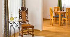 Das Kaminzimmer bildet den kommunikativen Mittelpunkt des Hauses. Der Boden besticht durch eine hochwertige Eiche-Landhausdiele – Baufritz Landhaus Braun