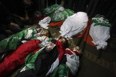Palestinians pray next to the bodies of members of the Dalou family during their funeral at a mosque in Gaza City. Eleven members of the Dalou family died when an Israeli air strike hit their house in Gaza City. Pictures Of The Week, Lightbox, Photojournalism, Mosque, Funeral, Bodies, Prayer, November, Colour