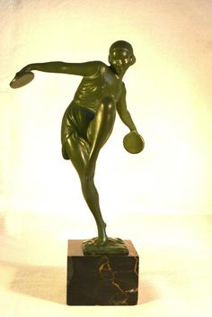 A green patinated figure of a female dancer with cymbals on a marble socle.  Height: 17 cm / 6,7 inch Period: about 1925