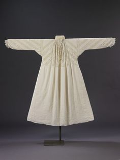 A woman's fine linen smock of the early 17th century is trimmed and inset with bobbin lace arranged in a distinctive diagonal pattern. The lace insertions are of the same design, but two different qualities, one finer than the other.
