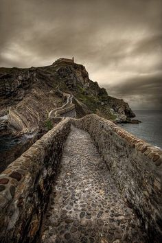 """San Juan de Gaztelugatxe, whose name means """"castle rock"""" in Basque, is a must if you are visiting the Basque Country (Spain). It is an island located just off the shore along the Bay of Biscay and it features a tiny church on its highest point, dedicated to John the Baptist. It is connected to the mainland by a man-made stone bridge that has 241 steps."""