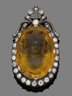 A citrine and diamond pendant. The oval citrine carved in relief to depict the bust of Diana, the moon goddess, within an old brilliant-cut diamond surround, to a similarly-set bow and coronet surmount. Victorian or Victorian style.