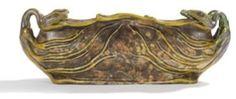 Zsolnay Pécs jardinière en céramique émaillée de marbrures polychromes au décor, démarrant en relief sur la panse et se poursuivant en ronde-bosse sur les extrémités, d'hydres à deux têtes de serpent, traitées iridescentes. Circa 1900. Porte le cachet écusson ZSOLNAY Pecs et la lettre M en creux et l'étiquette papier d'origine sous la base. 12 x 35 x 11 cm 14/22eE