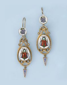 AN ANTIQUE MICROMOSAIC SUITE   The brooch set with an oval micromosaic panel depicting a beetle with foiled enamel wings, within a reeded tubular mount with circular blue and white mosaic panels to a fine chain; the earrings of similar design, circa 1880