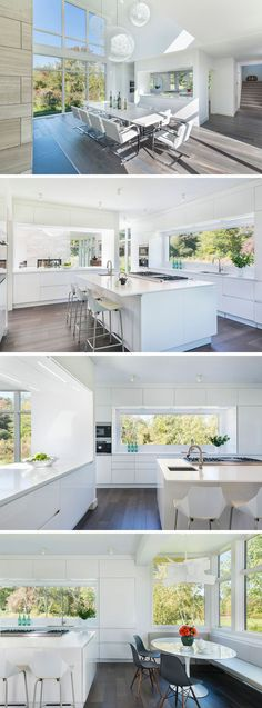 A pass-through window provides views from the dining room into this modern all-white kitchen that features a large window above the sink, a central island and a breakfast nook with a built-in corner bench.