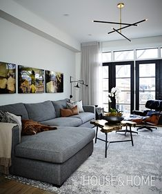 At first glance this living room, painted in Benjamin Moore's Classic Gray, doesn't scream fall. However, we think the live-edge style coffee table, artwork by Brent Orr and expansive sectional feel cozy and inviting — two characteristics of the season. | Photographer: Angus Fergusson | Designer: Cindy Bleeks