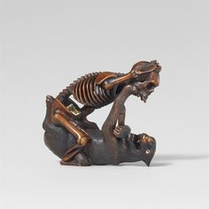 A Hida school boxwood netsuke of a skeleton and a wolf, in the style of Shôko. Late 19th century  The human skeleton is giving the wolf a beating, the wolf lying on its back and warding off the blows. The eyes of the wolf of bone and black glass.  Height 4.3 cm