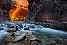The Lonely Virgin - The Virgin River winds it's way through a particularly dark section of 'The Narrows' slot canyon as the sandstone walls illuminate the reflected light deep within the amazing landscape of Zion National Park, Utah.  Shot in a single exposure.   November, 2010.