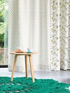 Fibre Naturelle -  Henley Fabric Collection - White curtain with olive green scallops, white curtain with green florals, turquoise crocheted rug, and a small wood table