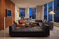 Floor-to-ceiling windows on the outside walls of this urban apartment take in the panoramic skyline views. Inside, sleek minimalist decor keeps the focus on the setting while also providing a place to unwind from the busy city day.