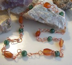 """Agate and Emerald Copper Necklace by AlisonsGemstones on Etsy 24"""" Chunky yet delicate Red Agate and Emerald Copper Necklace The Red / Fire agate is a wonderful grounding stone. This stone is thought to offer tremendous support during difficult times by protecting and offering a feeling of security. It deflects harm and enhances meditation. Emeralds are known to be inspirational and have been knick named the """" stone of successful love"""" It is believed to enhance and encourage overall calm."""