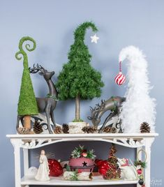 Whimsical Tabletop Christmas Trees--As long as you have some crafting wire and some aluminum foil, you are covered. So let's start making some whimsical tabletop Christmas trees, shall we? Apart from the curtain rod finials, I used a hot glue gun, Styrofoam cone forms (or you can use a paper-mache one like I did with one of them), some aluminum foil and thick craft/floral wire, an old faux pine garland, 2 white feather boas from the Dollar Store and some sheet moss I had on hand.