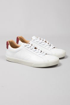 Veja White Puxa Marsala Esplar Bastille Leather Trainers: The mission of Danish brand, Veja, is to create a supply chain in the manufacture of their products that respects both humans and the environment. The designers work with all natural materials, including tapping rubber from trees without the use of industrial processes and buying cotton from organic farmers in Brazil to weave canvas for the brand's footwear collections. Sustainability and trading fairly is at the heart of the brand's…