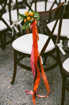Fresh fruit decorate the aisle chairs at an outdoor wedding ceremony