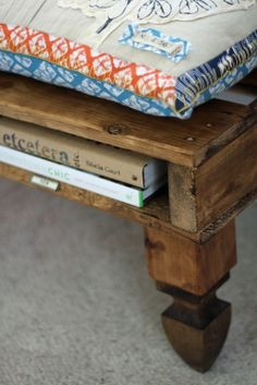 Pallet couch with space for books and decorative feet to lift it off the ground