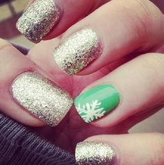 Green and silver themed Christmas nail art. Paint matte green and silver glitter on your nails. Add a snowflake in white polish for accent.