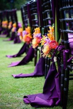Purple Wedding Flowers Purple orchid Wedding - Orange, yellow and red floral arrangements hung on black chairs with purple drapery Purple Orchid Wedding, Purple Orchids, White Orchids, Wedding Orange, Fall Wedding Purple, Sunset Wedding Theme, Purple Orange Weddings, African Wedding Theme, Tropical Wedding Reception
