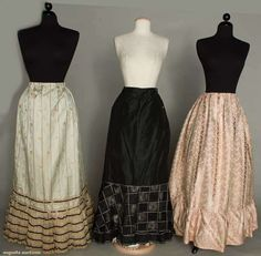 Three silk petticoats, c1890; All three with deep flounced hems and draw string waists; two brocade; One lilac and cream and one aqua, pink and green; One black taffeta with black lace lattice flounce